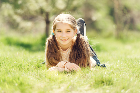 girl lying: cute smiling little girl lying on the grass in park looking away