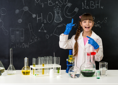 scientific research: schoolgirl in chemistry lab in white gown pointing at formula on blackboard near table with reagents