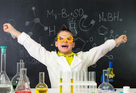 discovery: excited schoolboy with hands up in chemistry lab made a discovery