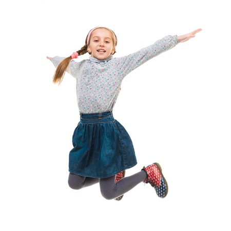 children clothing: photo of joyful little girl jumping isolated on white background