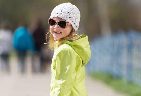Retrato de niña sonriente en gafas de sol en un parque en primavera