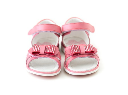 girl shoes: tiny pink sandals with bow isolated on white background