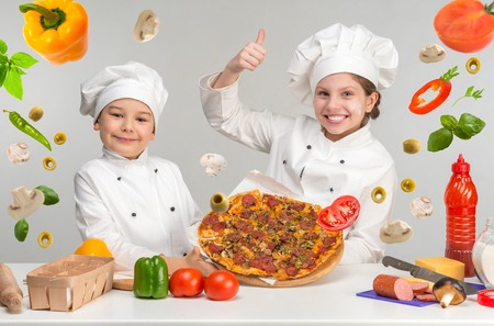 little boy and girl in white uniform of chef by the table with flying pizza Foto de archivo