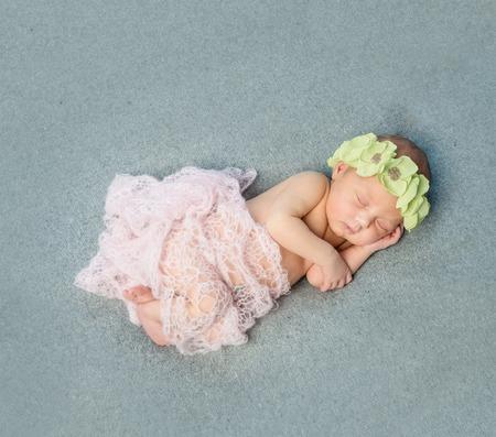 tender: tender newborn baby sleeping with wreath on head on blanket