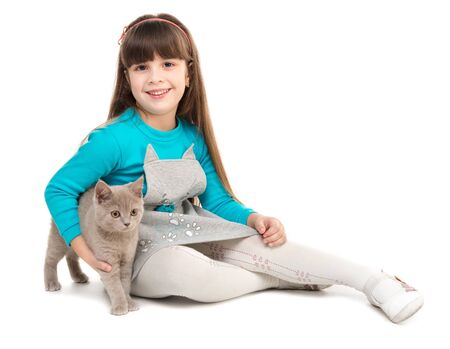 little  girls: cute little girl sitting on the floor with cat in hands isolated on white background Stock Photo