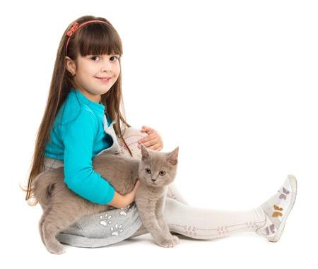 niños sentados: linda niña sentada en el suelo con el gato en las manos aisladas en el fondo blanco
