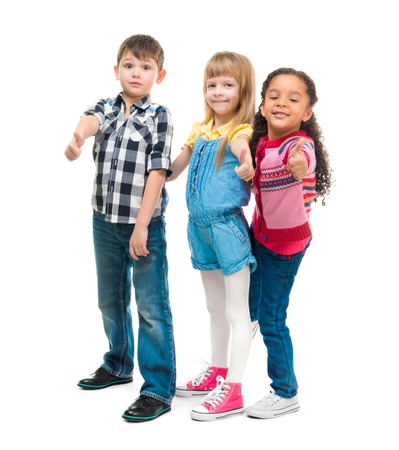 standing together: three smiling little children standing together isolated on white background
