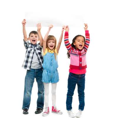 children background: three children with open mouths holding empty sheet of paper isolated on white background Stock Photo
