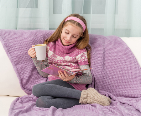 kid book: little cute girl on sofa with warm blanket and cup watching a magazine Stock Photo