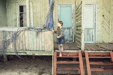wooden stairs: cute little girl standing on stairs of abandoned wooden house at a seaside Stock Photo