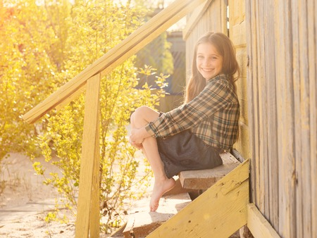 little girl barefoot: cute smiling little girl sitting on wooden stairs of house barefoot