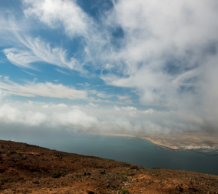 neighboring: cloudy sky and view on the sea and neighboring isle coastline from Lanzarote, Canary Isles, Spain