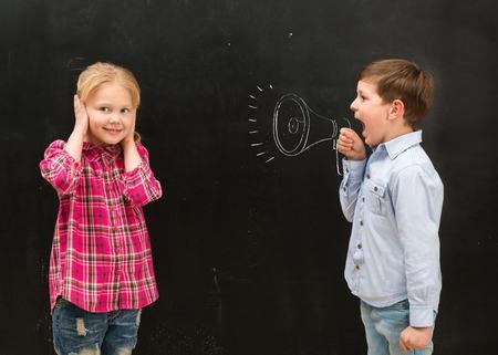 niños actuando: poco niño gritando en exhausto en la boquilla pizarra y niña tapándose los oídos con las manos