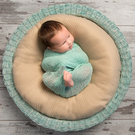 newborn baby: wrapped newborn baby with bare foot lying in round cot, top view Stock Photo