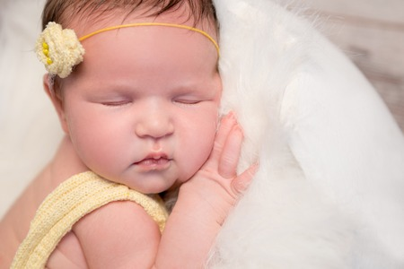 legs crossed: lovely newborn baby in yellow romper and headband sleeping with legs crossed Stock Photo