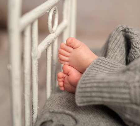 painted toes: funny bare baby feet out of gray pants on old cot with headboard, closeup