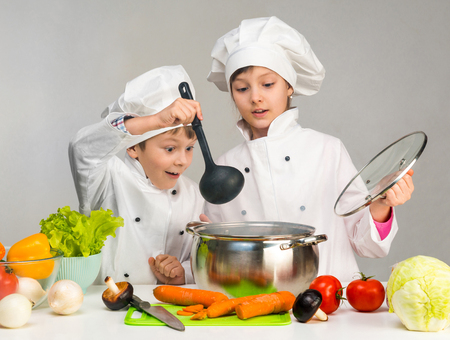 cooking little boy and girl looking in pan on table with vegetables Stock Photo