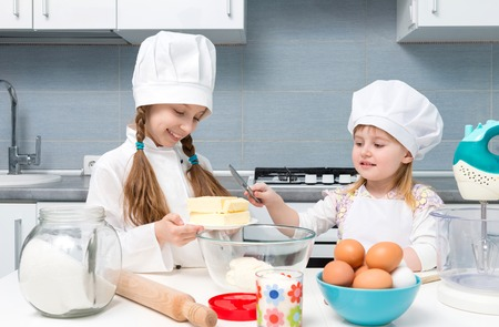 little dough: two smiling little girls-cooks cutting butter for dough on kitchen table Stock Photo
