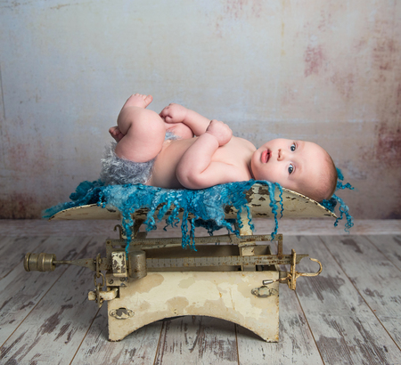 legs up: cute little baby with legs up lying on child scales on wooden floor