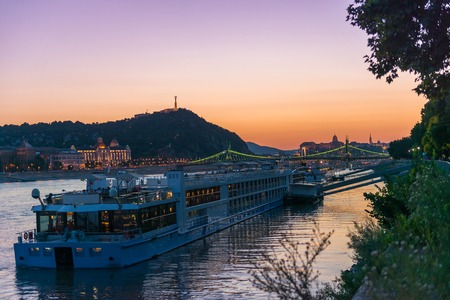 big touristic steamboat on Danube at sunset with cityscape of Budapest on the background