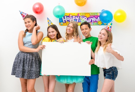 group of teenagers at a birthday party holding white banner