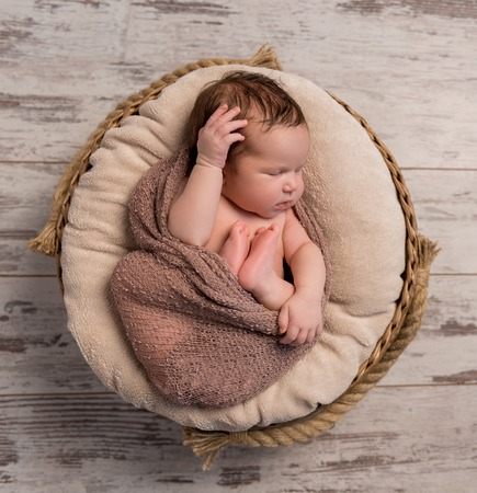 legs folded: wrapped sleepy baby with folded legs and hands on head, top view