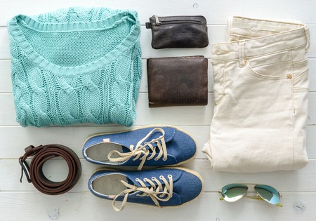 carefully folded woman casual closes and accessories on wooden table top view