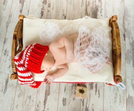 cot: sleeping newborn baby on a cot in colorful christmas decorations