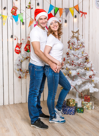 christmas hats: portrait of hugging beautiful young couple in red hats in decoraled christmas studio
