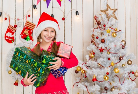 cute little girl in red hat holding presents in hands in decorated christmas studio