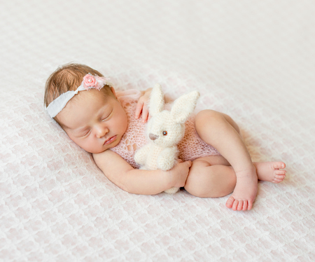 girl legs: lovely sleeping newborn girl with headband and holding toy on pink blanket