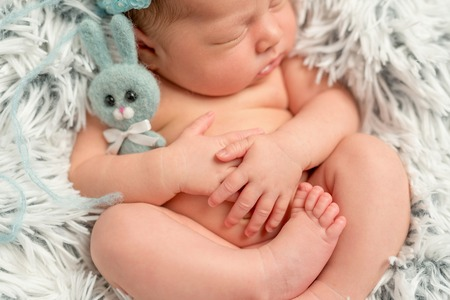 nude little girls: funny sleepy newborn baby holding little grey toy, closeup, top view Stock Photo