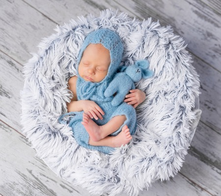 swaddled: lovely infant in hat and jumpsuit sleeping on round little bed, top view Stock Photo
