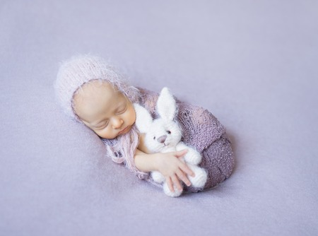 swaddled: swaddled sleeping newborn girl with white toy in hand