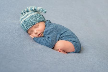 Slaap pasgeboren baby in blauwe gebreide jumpsuit en hoed met gekruiste benen Stockfoto - 64185786