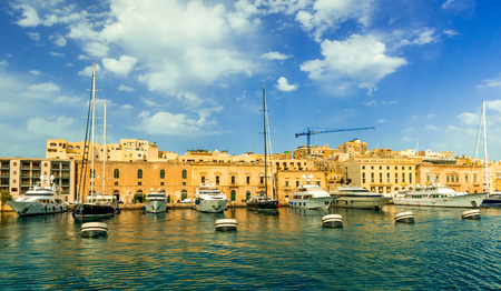 yellow walls: yachts anchored in Valletta bay with yellow city walls on the background, Malta