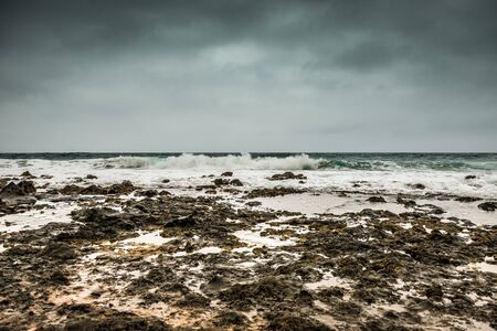stormy sea with foamy waves and gray sky on Lanzarote coastline landscape, Spain