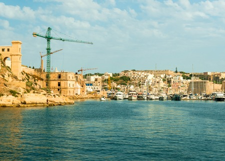 view of Valletta city and port with cranes and boats from the sea, Malta