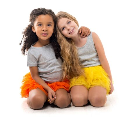 children clothing: two little smiling girls-friends with different complexion sitting on the floor isolated on white background Stock Photo