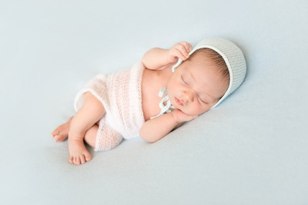 beautiful newborn baby sleeping with hands on head in hat, covered on blanket
