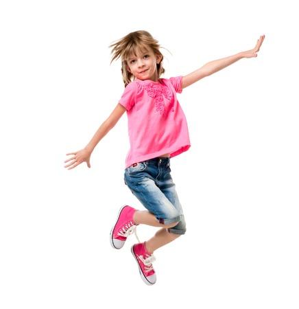 brincando: niña bonita en el salto de color rosa y riendo aislado en el fondo blanco Foto de archivo