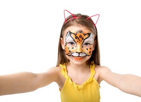 painted face: lovely little girl with colorful painted face like tiger making selfie Stock Photo
