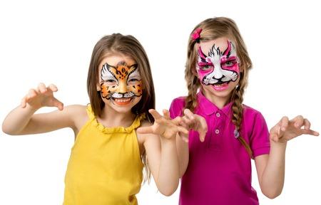 twee kleine meisjes met kleurrijk beschilderde gezichten grommen als dieren op een witte achtergrond