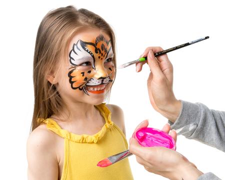 joyful little girl getting her face painted like tiger by artist Foto de archivo
