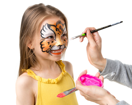 joyful little girl getting her face painted like tiger by artist Stock Photo