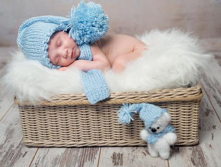 bebé en azul sombrero para dormir en la manta suave y esponjosa en la cesta de mimbre Foto de archivo