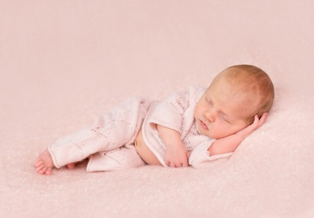 pink panties: cute sleeping newborn in panties and headband on his head on pink blanket