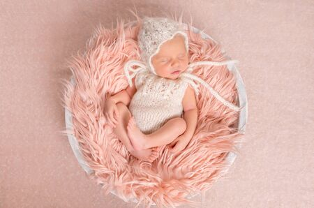 new baby: sweet newborn girl in white romper sleeping on round cot with fluffy blanket, top view