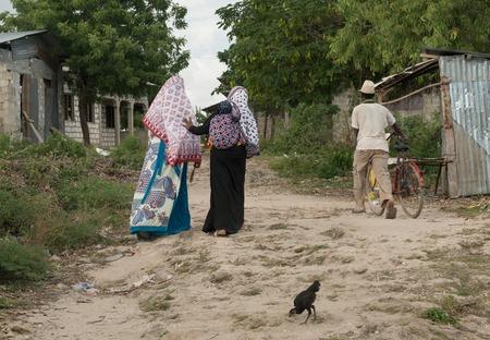 pass away: ZANZIBAR, TANZANIYA- JULY 13: people passing by in poor village on July 13, 2016 in Zanzibar, Tanzania