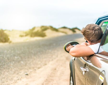 drive car: driver leaning out of car window on roadside in Lanzarote desert, Canary Island, Spain Stock Photo